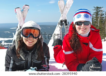 Two young mountain-skiers resting on the slope. - stock photo