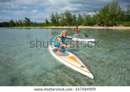 two young muscular surfers riding on the stand-up paddle board in the clear waters of the Indian Ocean  of Mauritius island on the background of green trees