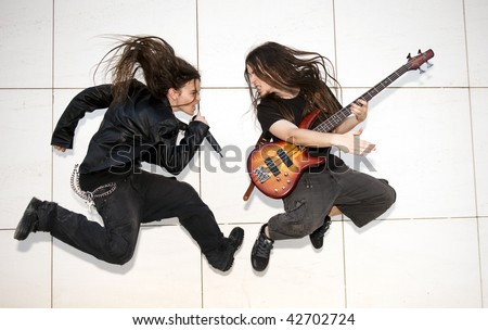 Two young musician jumping against white wall - stock photo