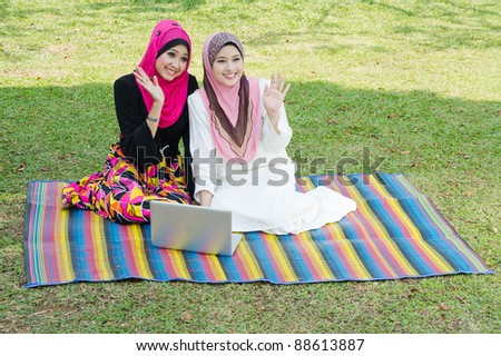 two young muslim woman say hi to their friends at park - stock photo