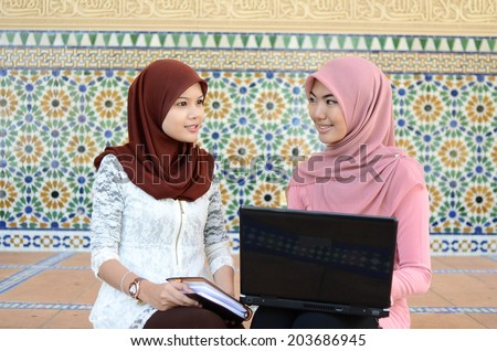 Two young Muslim women with beauty smile using computer laptop - stock photo