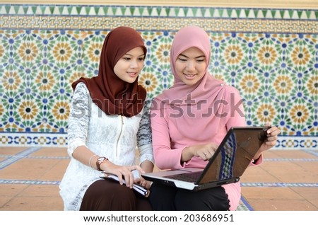 Two young Muslim women with beauty smile using computer laptop