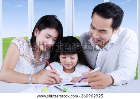 Two young parents assist their daughter doing school assignment at home - stock photo