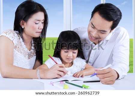 Two young parents help their daughter to learn how to write on the book, shot at home