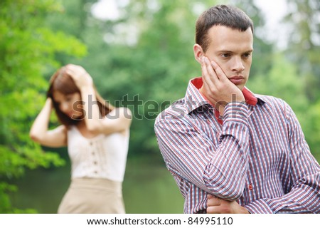 Two young pensive people having quarrel or facing some problems at summer green park. - stock photo