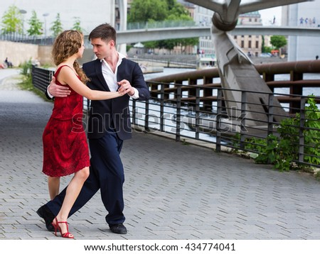 two young people - a man in black suit and a woman wearing red dress - dancing tango outside under the bridge - stock photo
