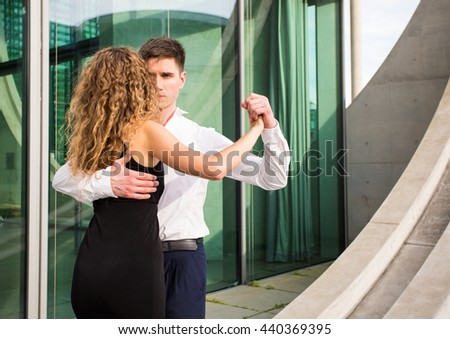 two young people - a man in white shirt and a woman wearing black dress - dancing tango outside - stock photo