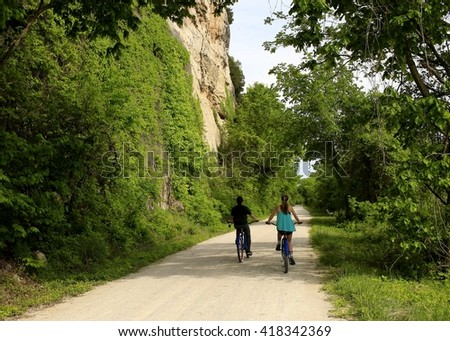 Two young people biking along the Missouri River; bluffs on the left and trees on the right - stock photo