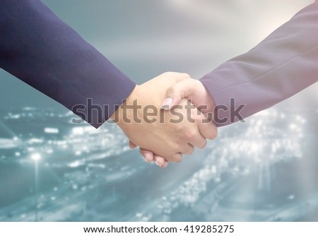 Two young people businessmen shaking hands with light fare. Business communication and cooperation concept. success in job or work or teamwork. congratulatation concept. - stock photo