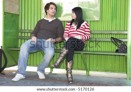 Two young people chatting at the bus stop.