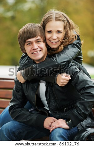 Two young people couple at autumn outdoors embracing each other - stock photo
