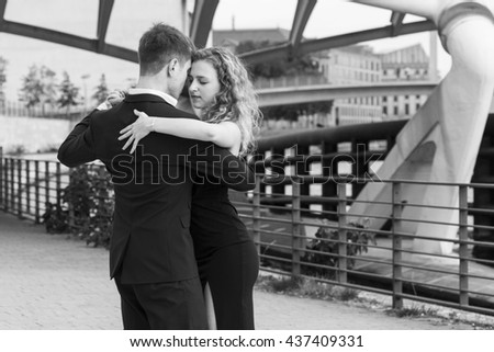 two young people dancing tango outside under the modern bridge; black and white - stock photo
