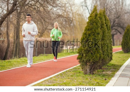 Two young people jogging on a running track in a park - stock photo