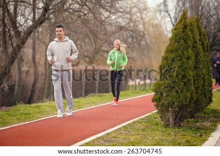 Two young people jogging on running track in the park - stock photo