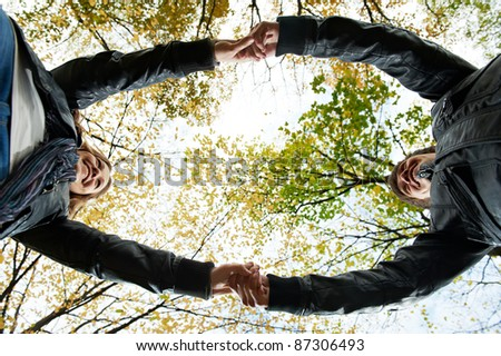 Two young people join hands in park at autumn outdoors date. Girl wear chaplet from maple - stock photo