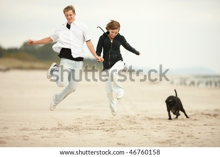 two young people jumping on the beach  and holding tight