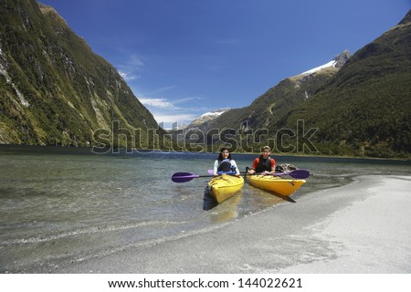 Two young people kayaking in the lake with mountains in background - stock photo