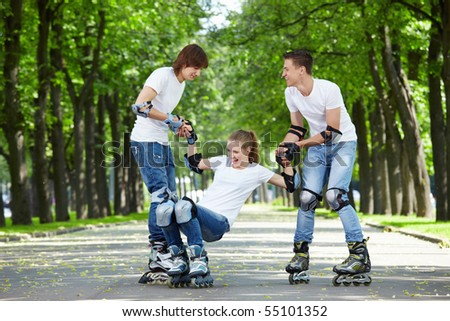 Two young people lift the fallen girl on rollers - stock photo