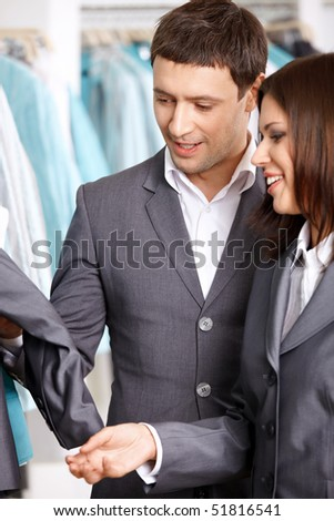 Two young people look clothes in shop - stock photo