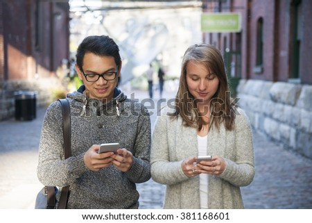 Two young people looking into smartphones while walking on city street - stock photo