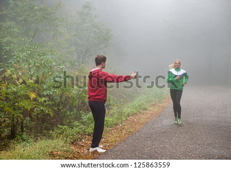 two young people making fun while jogging - stock photo