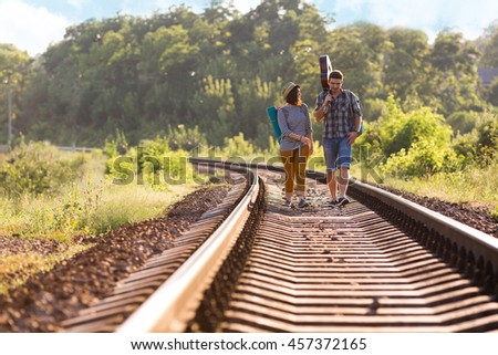 Two young People Man and Girl in casual Travel Clothing with Backpacks and Guitar walking along Railroad with back light Sun and Forest on Background - stock photo