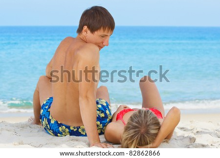 Two young people on the beach near sea - stock photo