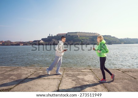 Two young people running in opposite directions by the Danube river in Novi Sad, Serbia - stock photo