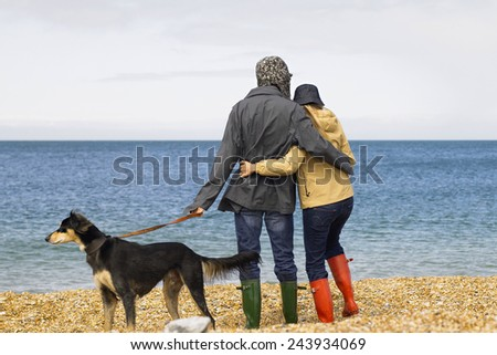 two young people running on the beach kissing and holding tight with dog - stock photo