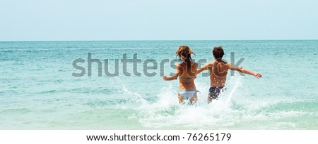 Two young people running to the blue sea - stock photo