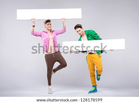 Two young people showing empty boards