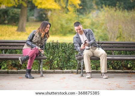 Two young people sitting on benches in a park and exchanging phone numbers