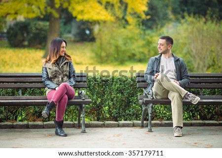 Two young people sitting on benches in a park and talking - stock photo