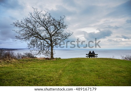Two young people sitting on the bench over the sea and looking at the calm scenery