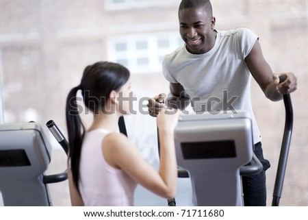 Two young people speaking while exercising at gym - stock photo