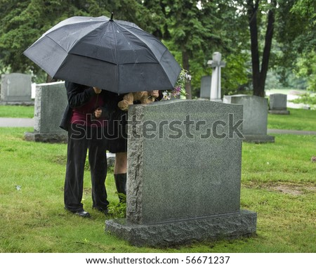 Two young people under an umbrella bringing a teddy bear and flowers to a grave site in the rain. - stock photo