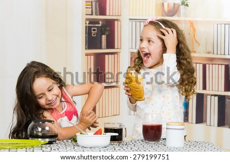Two young playful preschooler girls eating breakfast at the table - stock photo