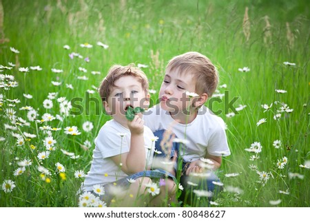 Two young preschool siblings playing in green field with blooming daisies.