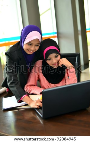 Two young pretty Asian muslim business woman in head scarf  busy at work