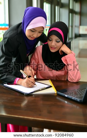 Two young pretty Asian muslim business woman in head scarf  with book and laptop