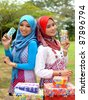Two young pretty Asian muslim college girl with boxes of present. - stock photo