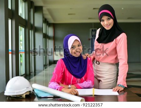 Two young pretty Asian muslim woman study together - stock photo