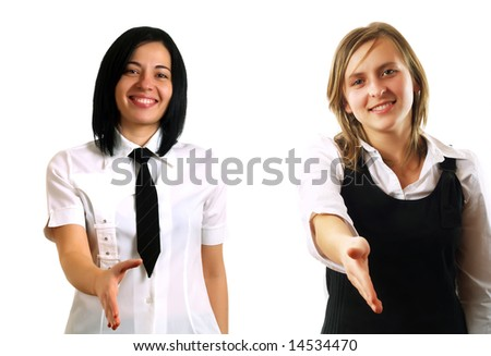 Two young pretty businesswomen are holding their hands out for handshaking. They are smiling and they are wearing elegant white shirts. - stock photo