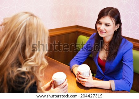Two young pretty caucasian girls with long hair chatting and having fun at a cafe - stock photo