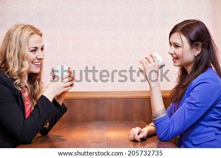 Two young pretty caucasian girls with long hair enjoying their coffee at a cafe - stock photo