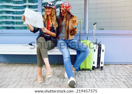 Two young pretty girls exploring and looking on map before their traveling adventures, smiling and having fun before new emotions. Best friend posing with their luggage. - stock photo