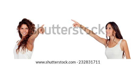 Two young pretty girls indicating something isolated on a white background - stock photo