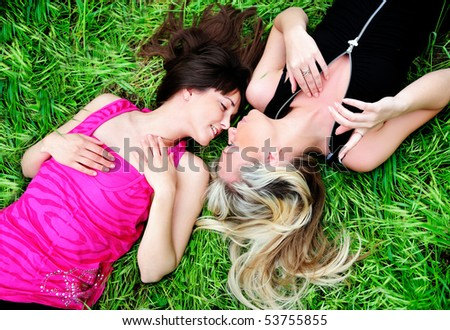 two young pretty girls laying in grass - stock photo