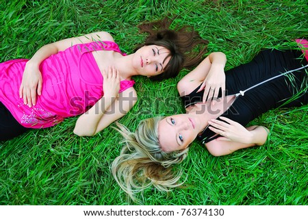 Two young pretty girls laying in grass. - stock photo