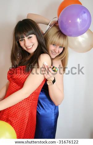 two young pretty woman in birthday cap with noisemaker - stock photo